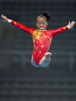 Deng Linlin forgets to remove pacifier before balance beam exercise.